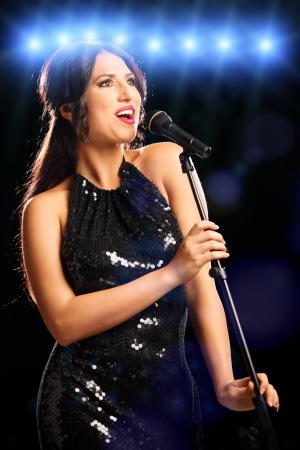 Glamorous young woman in black dress singing photo