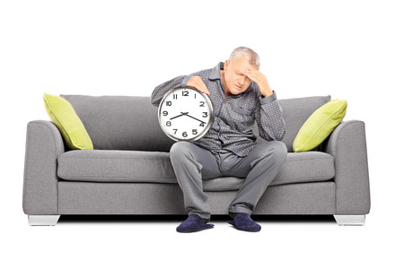 late 50s: Mature man in pajamas seated on a sofa holding a clock and having a headache isolated on white background