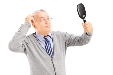 Middle aged gentleman checking for thinning hair in the mirror isolated on white background photo
