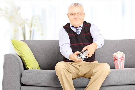 Senior man seated on a couch playing video games at home photo