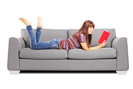 book reading: Young female lying on a sofa and reading a book isolated on white background
