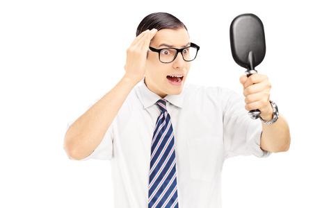 homme inquiet: Jeune homme inquiet v�rification de l'amincissement des cheveux dans le miroir isol� sur fond blanc