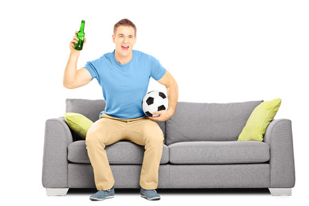 Happy cheerful male sport fan with football and beer watching sport isolated on white background photo