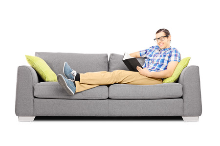 Young male on a sofa reading a book isolated on white background photo