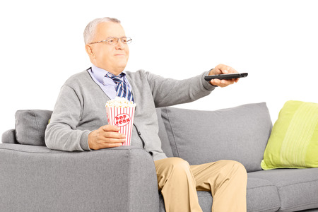 Senior gentleman sitting on a sofa and watching TV isolated on white background photo