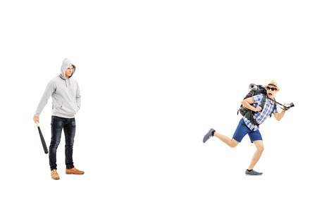 Guy with hood over his head holding a baseball bat and scared tourist trying to run away isolated on white background photo