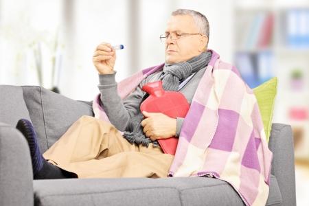 w�rmflasche: Krank reifer Mann auf einem Sofa mit einer W�rmflasche Blick auf Thermometer zu Hause Lizenzfreie Bilder