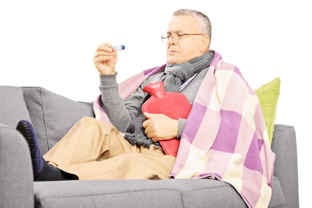 wärmflasche: Krank reifer Mann auf einem Sofa mit einer Wärmflasche Blick auf Thermometer isoliert auf weißem Hintergrund