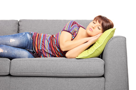 Young female sleeping on a sofa isolated on white background photo