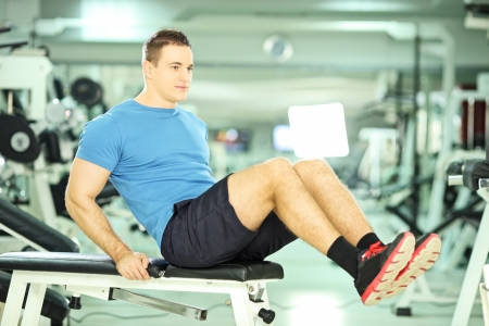 athletic wear: Young man seated on a bench exercising abdominal muscles in a fitness club Stock Photo