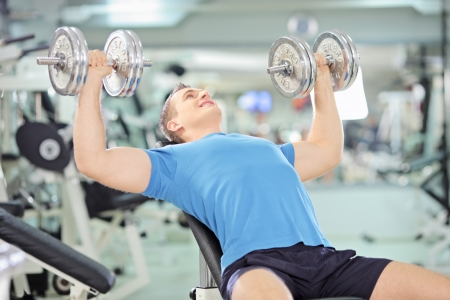 Young muscular man lifting weights in a gym photo