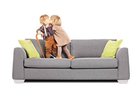 cane sofa: Girl kissing a boy while standing on a sofa isolated on white background