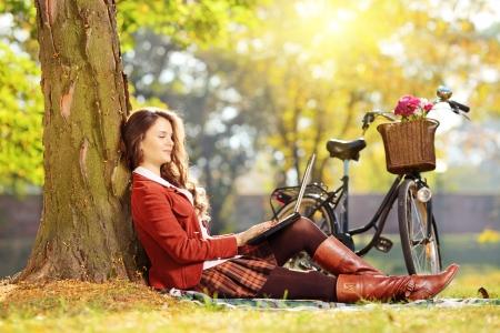 belle brunette: Femelle détendue travaillant sur un ordinateur portable assis sur l'herbe dans un parc sur une journée ensoleillée