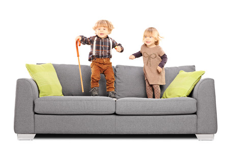 Brother and sister siblings standing and playing on a sofa isolated on white background photo