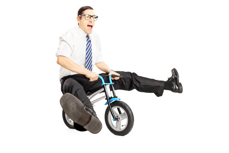 pedal: Nerdy young male with tie riding a small bicycle isolated on white background