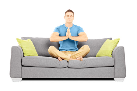 Young male meditating seated on a sofa isolated on white background photo