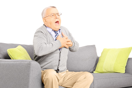 infarct: Senior man seated on a sofa having a heart attack, isolated on white background Stock Photo