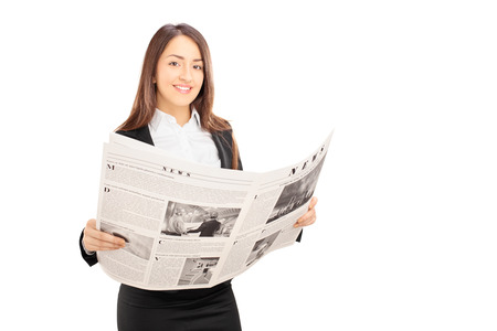 newspapers: Young businesswoman in black suit holding a newspaper isolated on white background