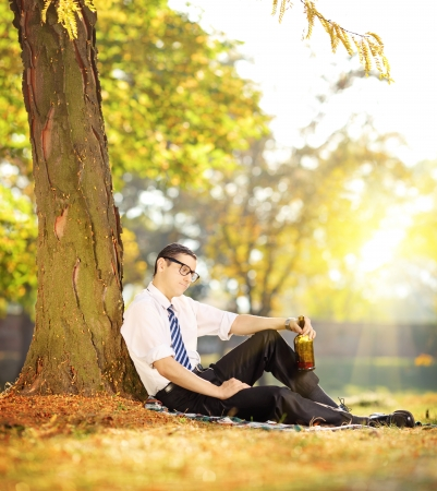 Disappointed young businessman sitting on a grass with bottle in his hand, in park, shot with tilt and shift photo