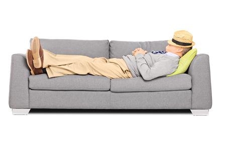 白い背景で隔離のソファーで眠っている彼の頭の上の帽子を持つ成熟した男