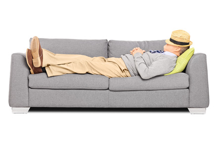 lying on couch: Mature man with hat over his head sleeping on a sofa isolated on white background