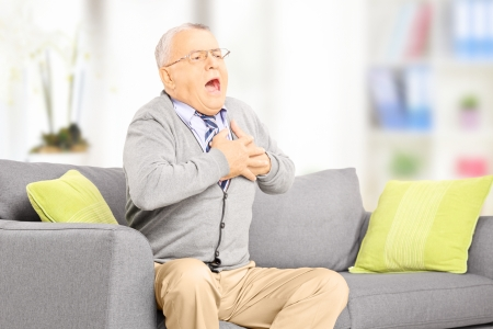 Senior man seated on a sofa having a heart attack at home photo