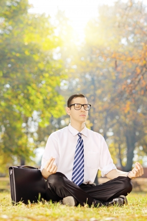 Young businessperson seated on a green grass meditating in a park on a sunny day photo