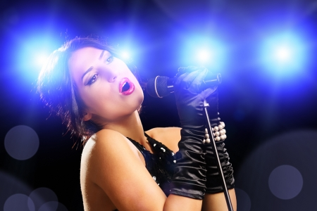 stage performer: Beautiful young female singer in black dress singing on a stage Stock Photo