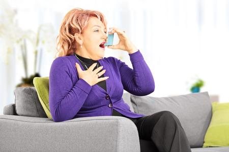 Rijpe vrouw zit op een bank nemen de behandeling van astma met inhalator thuis Stockfoto