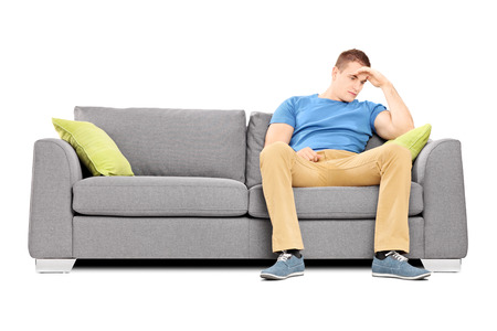 dissappointed: Dissappointed young man sitting on a sofa isolated on white background Stock Photo
