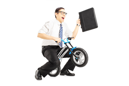 Excited young businessman with leather suitcase riding a small bicycle isolated against white background photo