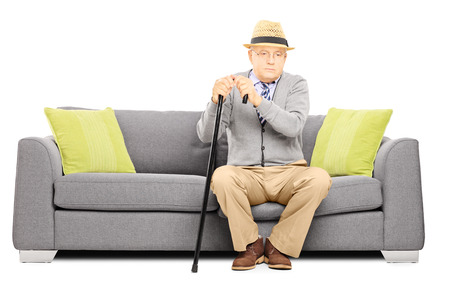 cane sofa: Thoughtful senior man with a cane sitting on a sofa isolated on white background