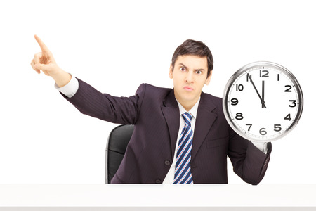 Angry businessman holding a clock and gesturing with his finger, isolated on white background photo