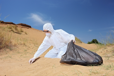 Male worker in protective suit holding a waste bag and collecting samples from sand, symbolizing pollution Reklamní fotografie