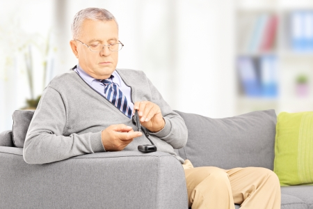 glucometer: Mature diabetic patient seated on a sofa measuring sugar level in blood using glucometer at home
