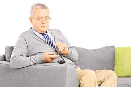 Mature diabetic patient seated on a sofa measuring sugar level in blood using glucometer isolated on white background