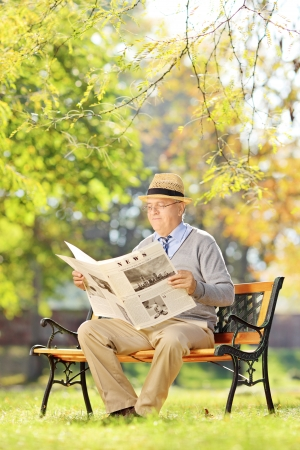 Senior gentleman with hat sitting on a bench and reading a newspaper in a park photo