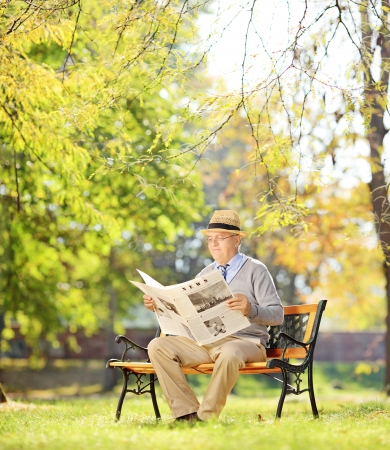 Senior gentleman with hat sitting on a wooden bench and reading a newspaper in a park, shot with tilt and shift photo