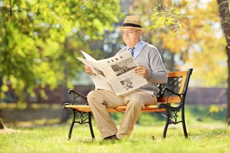 oude krant: Senior man zittend op een houten bank en het lezen van een krant in de herfst Stockfoto