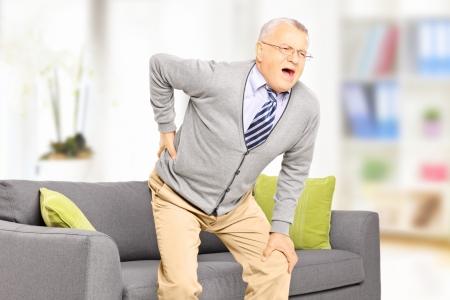 espada: Hombre mayor que sufre de dolor de espalda en casa Foto de archivo