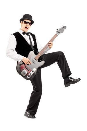 euphoric: Piena lunghezza ritratto di un uomo euforico suonare una chitarra basso isolato su sfondo bianco