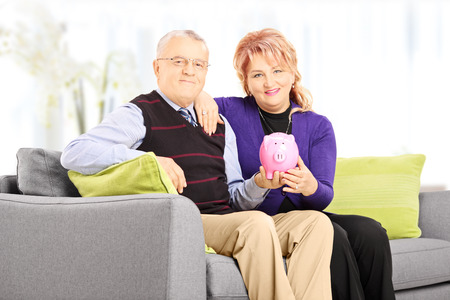 Mature man and woman sitting on a sofa and holding a piggy bank at home Stock Photo - 24124859