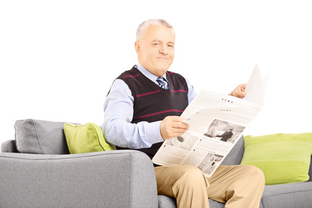 Senior gentleman on a modern sofa with newspaper looking at camera isolated on white background Stock Photo - 24124970