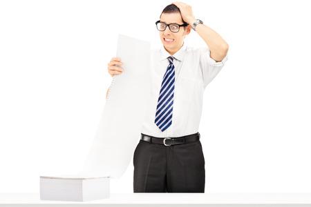 caras emociones: Empresario joven sorprendido mirando factura muy cara aisladas sobre fondo blanco Foto de archivo