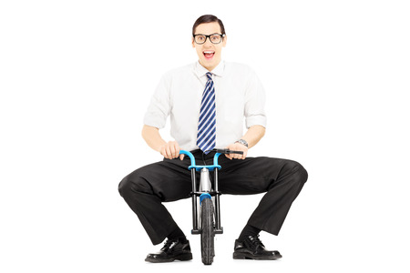 Smiling young businessman riding a small bicycle isolated on white background photo