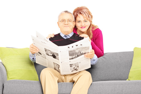 Wife hugging her husband seated on a sofa with newspaper isolated on white background photo