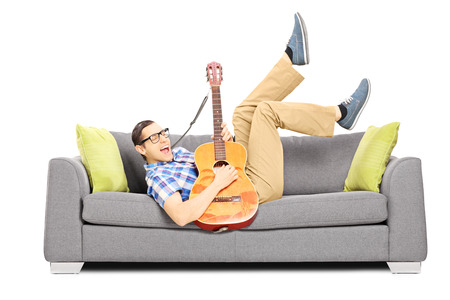 Excited young male lying on a modern sofa and playing an acoustic guitar isolated on white background photo