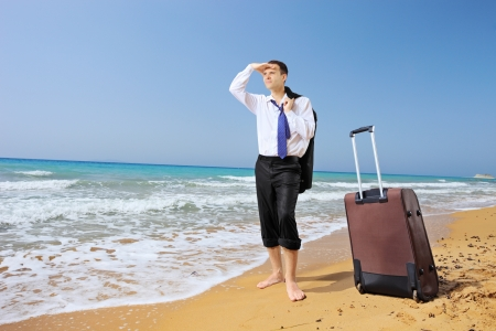 Full length portrait of a lost businessman with his luggage searching for way on a sandy beach photo