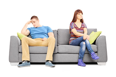 uninterested: Sad heterosexual couple sitting on a sofa after an argument isolated on white background