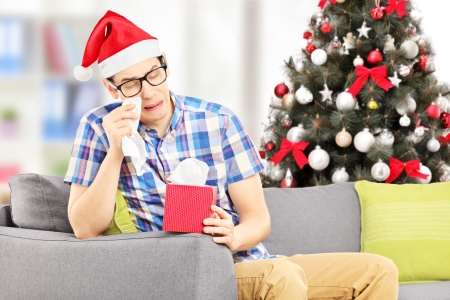 Sad young male seated on a sofa wiping his eyes from crying with christmas tree in the background